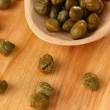 Green capers in wooden spoon on wooden background close-up — Stock Photo #14080985