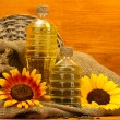 Oil in bottles, sunflowers and seeds, on wooden background — Stock Photo #14081003