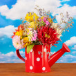 Stock Photo: Red watering cwith white polka-dot with flowers on sky background