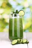 Glass of cucumber juice on wooden table, on green background — Stock Photo