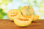 Cut melon on wooden table on green background — Stock Photo