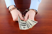 Businessman in handcuffs counts the money for bribes — Stock Photo