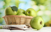 Ripe green apples with leaves in basket, on wooden table, on green backgrou — Stock Photo