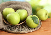 Ripe green apples in basket on burlap, on wooden table, on green background — Stock Photo