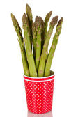 Fresh asparagus in colorful pot isolated on white — Stock Photo