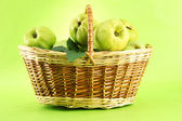 Sweet quinces with leaves in basket, on green background — Stock Photo