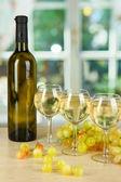 Witte wijn in glas met fles op achtergrond van venster — Stockfoto
