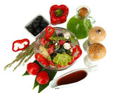 Fresh greek salad in glass bowl surrounded by ingredients for cooking isola — Stock Photo
