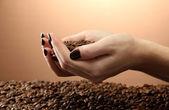 Kvinnliga händer med kaffebönor, på brun bakgrund — Stockfoto