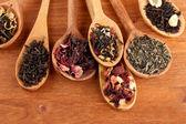 Sortiment von trockenen Tee im Löffel, auf hölzernen Hintergrund — Stockfoto