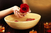 Woman hands with wooden bowl of water with petals, on brown background — Stock Photo