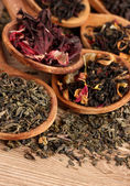Assortimento di tè asciutto in cucchiai, su fondo in legno — Foto Stock