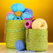Colorful yarn for knitting in green basket on orange background — Stock Photo