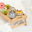 Wooden tray with light breakfast on bed — Stock Photo