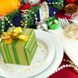 Small Christmas gift on plate on serving Christmas table background close-u - Stock fotografie