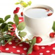 Cup of tea with hip roses, on wooden table — Foto de Stock