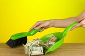 Sweeps money in the shovel on colorful background close-up — Stock Photo