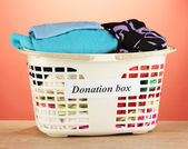 Donation box with clothing on red background close-up — Foto de Stock