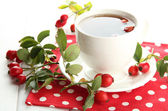 Kopp te med hip rosor, på träbord — Stockfoto