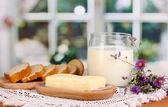 Boter op houten houder omringd door brood en melk op achtergrond van venster — Stockfoto