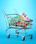 Shopping trolley with pills, on blue background — Stock Photo