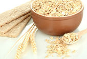 Brown bowl full of oat flakes with spikelets, oat biscuits and wooden spoon — Stock Photo