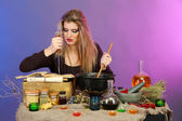 Halloween witch stirring in poison soup in her cauldron on color background — Stock Photo