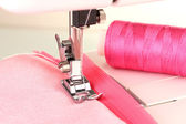 Closeup of sewing machine working part with pink cloth — ストック写真