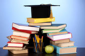 Books and magister cap against school board on wooden table on blue backgro — Stock Photo