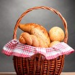Stock Photo: Delicious bread in basket on wooden table on gray background