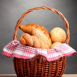 Delicious bread in basket on wooden table on gray background - Stock Photo