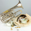 Musical instrument with money on gray background - Stock Photo