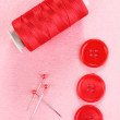 Stock Photo: Colorful sewing buttons with thread on pink fabric