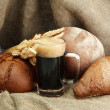 Tankard of kvass and rye breads with ears, on burlap background — Stock Photo #14303075