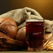 Tankard of kvass and rye breads with ears, on wooden table on brown background — Stock Photo #14303085