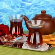 Stock Photo: Glass of Turkish tea and kettle on color background