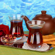 Glass of Turkish tea and kettle on color background — Stock Photo