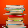 Stack of interesting books and magazines on wooden table on red background - Stock Photo