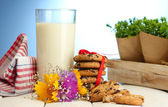 Glass of milk, chocolate chips cookies with red ribbon and wildflowers on wooden table on blue background — Stock Photo