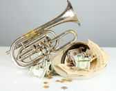 Musical instrument with money on gray background — Stock Photo