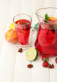 Sangria in jar and glass with fruits, on white wooden table — Stock Photo