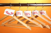 Wooden clothes hangers as sale symbol on orange background — Stock Photo