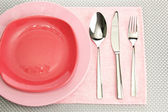 Pink empty plates with fork, spoon and knife on a grey tablecloth — Stock Photo