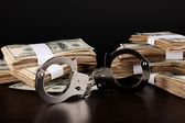 Handcuffs and packs of dollars on wooden table close-up — Stock Photo