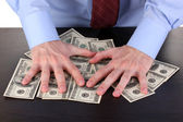 Male hands hold dollars on a wooden table close-up — Stock Photo