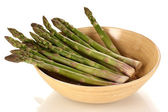 Fresh asparagus in wooden bowl isolated on white — Stock Photo