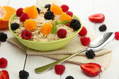 Tasty oatmeal with berries and fruits, on white wooden table — Stock Photo