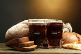 Tankards of kvass and rye breads with ears, on wooden table on brown background — Stock Photo