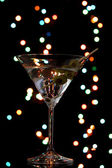 Martini glass and olives on dark bright background — Stock Photo