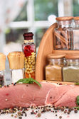 A large piece of pork marinated with herbs and spices on white table on window background — Stock Photo